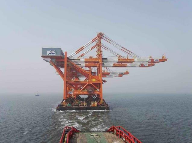 安全引领装载4台岸吊的无动力驳船出港